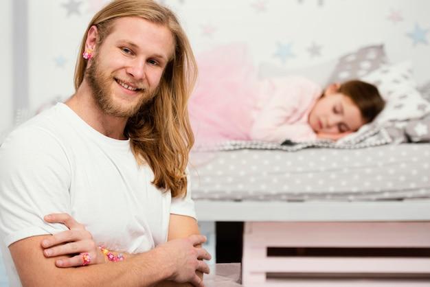 Pai sorridente posando ao lado da filha sonolenta em casa
