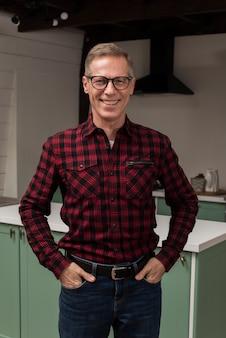 Pai sorridente posando na cozinha