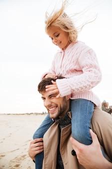 Pai sorridente se divertindo com sua filha pequena