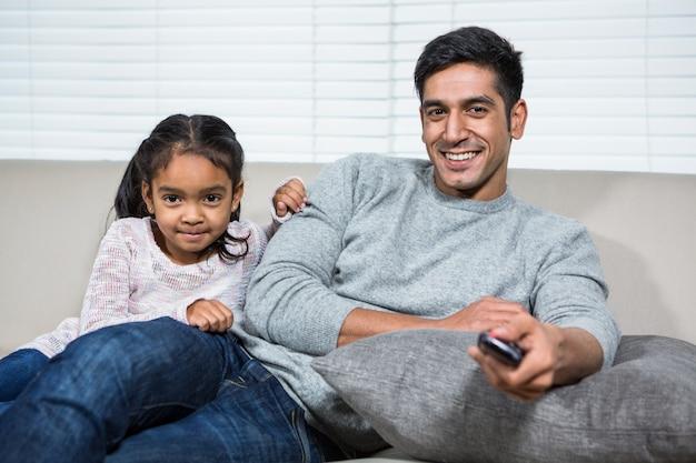 Pai sorrindo assistindo televisão com a filha no sofá