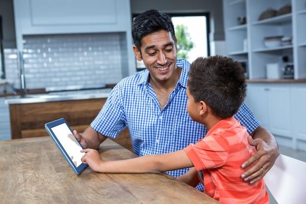 Pai sorrindo usando tableta com seu filho