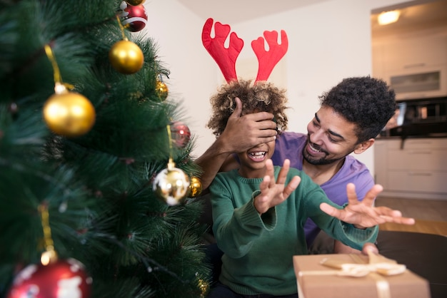 Pai surpreendendo a filha com presente perto da árvore de natal