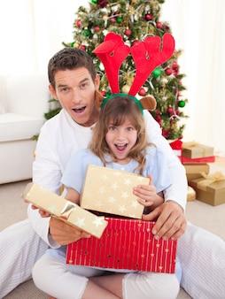 Pai surpreendido e sua menina que abre presentes de natal