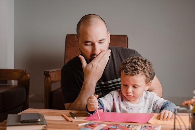 Pai surpreso ao ver como seu filho desenha nas folhas de papel