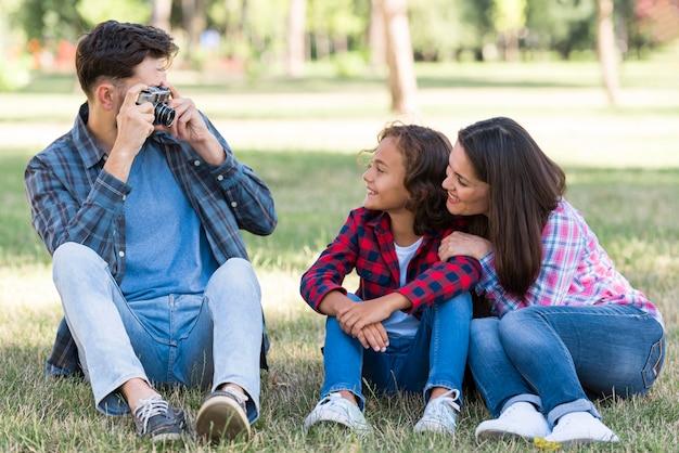 Pai tirando foto do filho e da mãe no parque