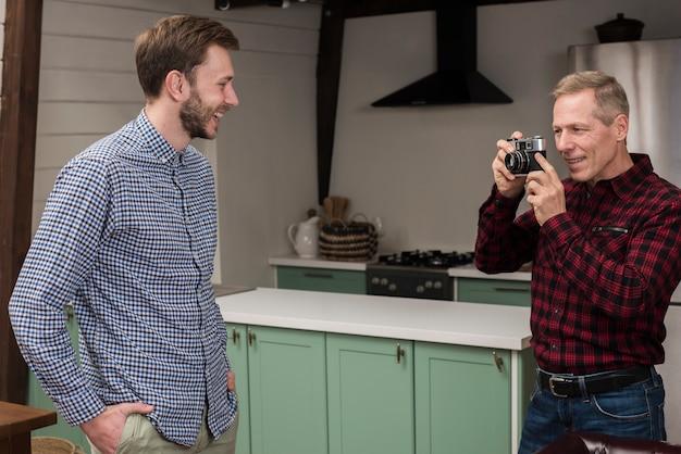 Pai tirando fotos do filho feliz na cozinha
