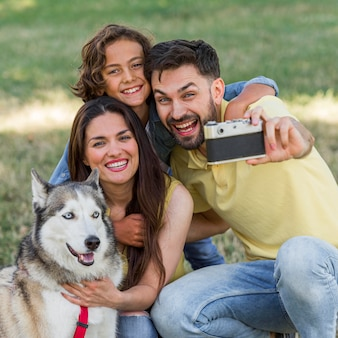 Pai tirando selfie da família e do cachorro enquanto está no parque