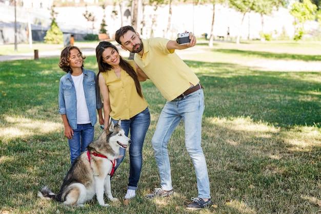 Pai tirando uma selfie da esposa e filho no parque com o cachorro