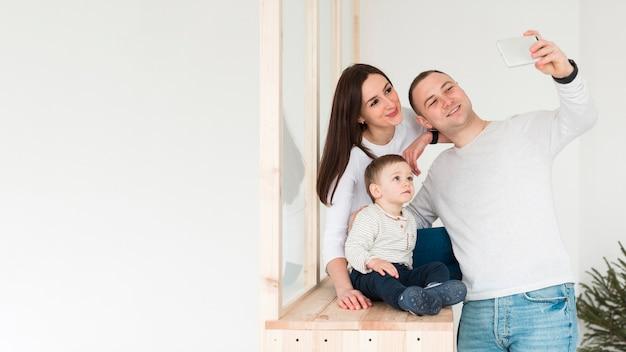 Pai tirando uma selfie de família com mãe e filho