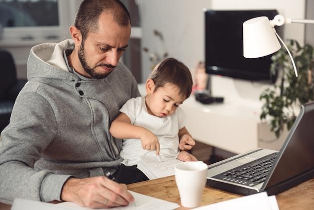 Pai trabalhando em casa e segurando o filho no colo
