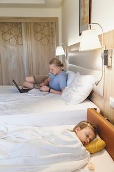 Pai trabalhando enquanto filho escorregando na cama do hotel
