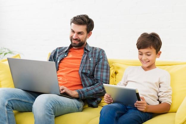 Pai trabalhando no laptop e filho olhando no tablet