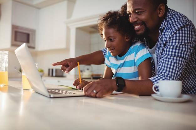 Pai usando laptop enquanto ajuda a filha com a lição de casa