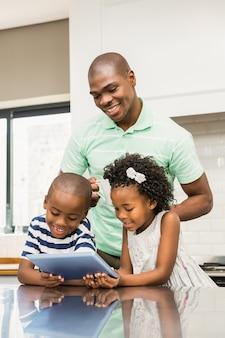 Pai usando tableta com seus filhos na cozinha
