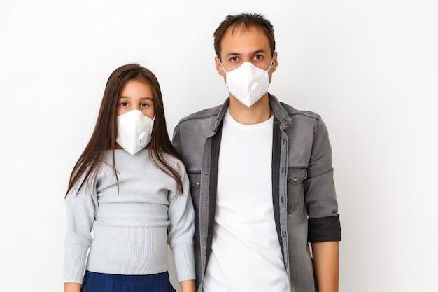 Pai usando uma máscara facial higiênica descartável para sua filha para proteção contra a propagação da doença em fundo branco. prevenção da propagação do vírus corona covid-19, gripe resfriado ou poluição.