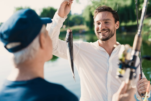 Pai velho com filho de barba pesca no rio.