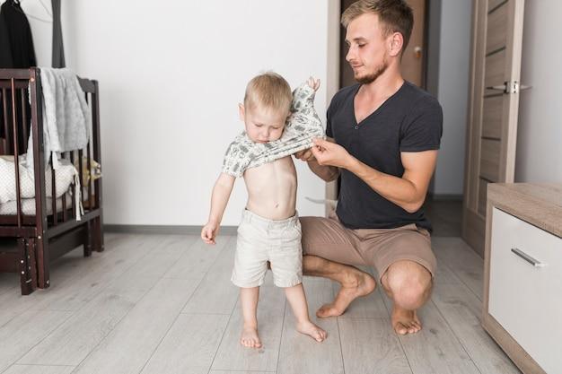 Pai vestindo camiseta para seu filho pequeno em casa