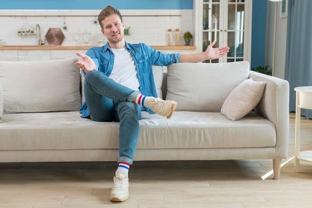 Pai, vestindo roupas casuais e sentado no sofá