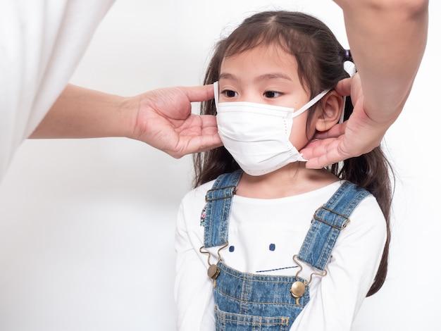 Pai vestindo uma máscara de higiene para sua filha para proteção espalhar o coronavírus ou covid-19 na parede branca.