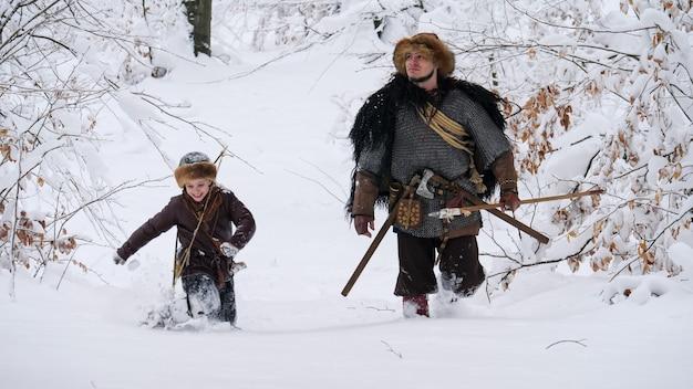 Pai viking com seu filho indo na floresta de inverno, eles tendo machado, lança, cebola. eles se vestiram com roupas medievais.