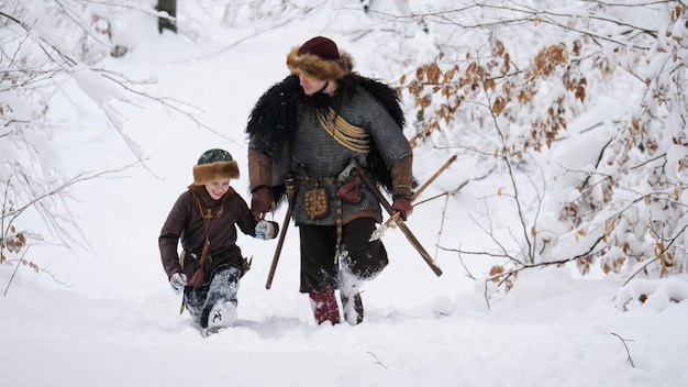 Pai viking com seu filho indo na floresta de inverno, eles tendo machado, lança, cebola.