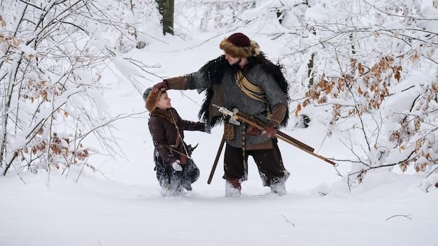 Pai viking com seu filho indo para a floresta de inverno