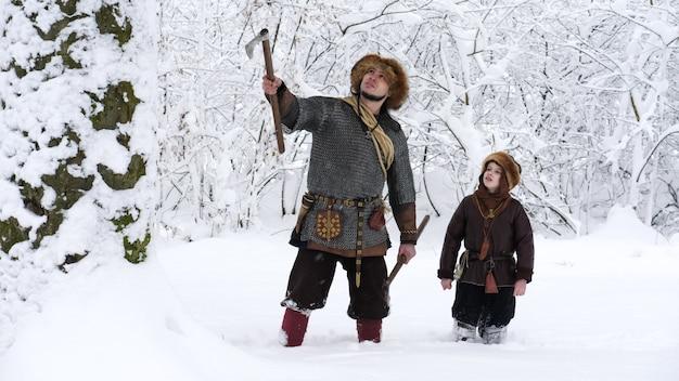 Pai viking com seu filho na floresta de inverno. pai conversando com seu filho, segurando o machado de mãos. eles se vestiram com roupas medievais.