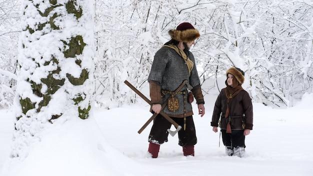 Pai viking com seu filho na floresta de inverno.