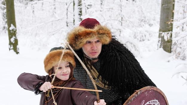 Pai viking ensina seu filho a arco e flecha na floresta de inverno