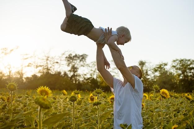 Pai vomita seu filho pequeno no campo de girassóis contra o céu