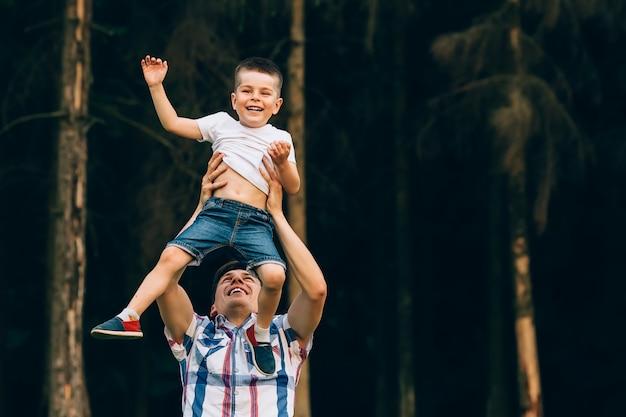 Pai vomitando seu filho pequeno no ar. tempo em família juntos