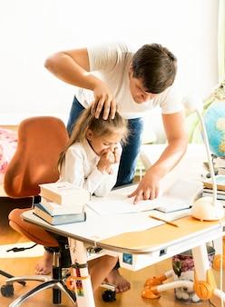 Pai zangado apontando para um erro no caderno das filhas