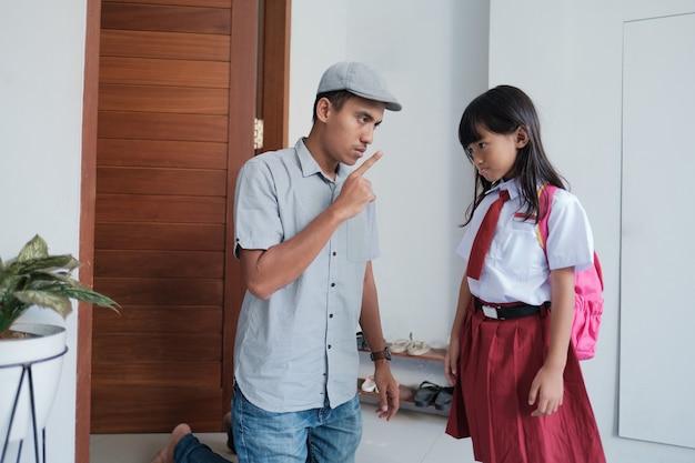 Pai zangado confronta seu filho depois da escola. problema do aluno primário asiático. pai abusivo com filha