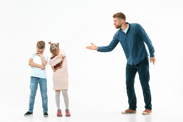 Pai zangado repreendendo filho e filha em casa