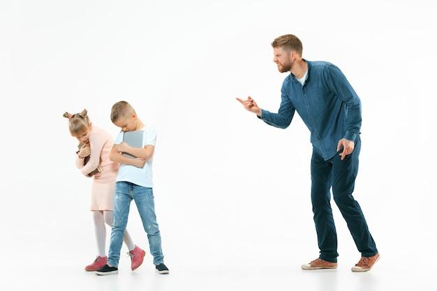 Pai zangado repreendendo o filho e a filha em casa.