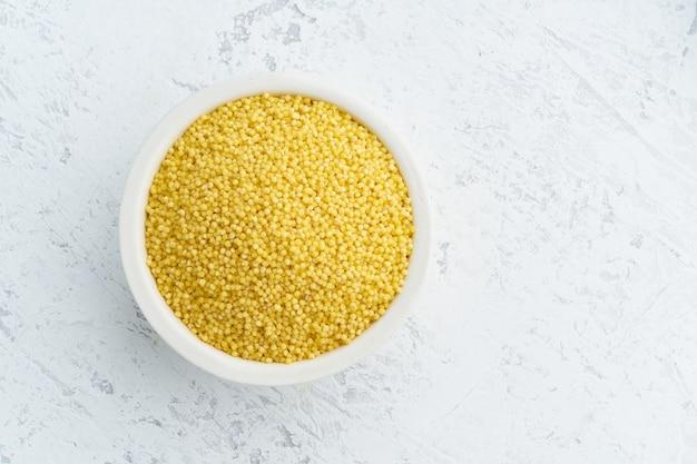 Painço, junco na bacia branca no branco. cereais secos e sem lectina em copo, comida vegana