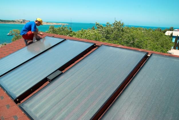 Painéis de aquecimento solar de água do trabalhador no telhado.