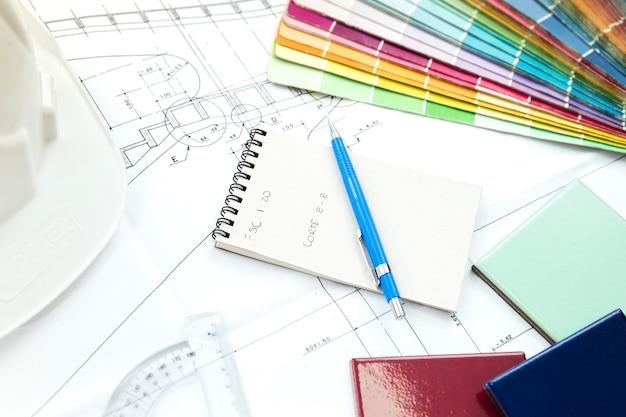 Painéis de fachada perto de caneta e caderno na mesa