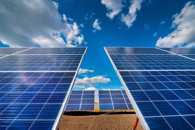 Painéis de usinas solares, com reflexo de nuvens e céu