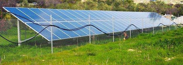 Painéis solares colocados num prado rural.