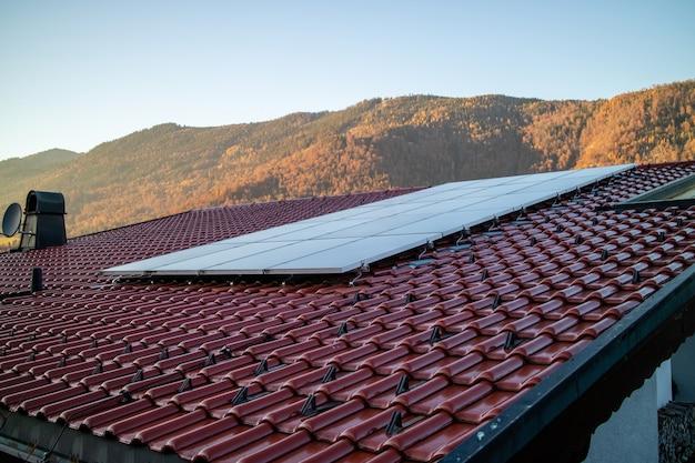 Painéis solares de energia alternativa em um telhado de telhas em um fundo de montanhas de pedra e céu azul claro em dia de outono, na áustria.