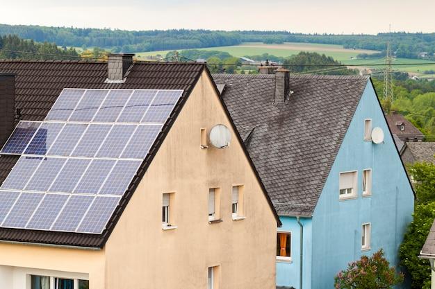 Painéis solares eficientes de poupança de energia verde limpa e renovável no telhado da casa suburbana.