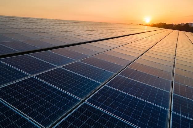Painéis solares fotovoltaicos azuis montados no telhado do prédio para a produção de eletricidade ecológica limpa ao pôr do sol. produção do conceito de energia renovável.