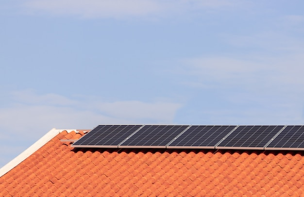 Painéis solares fotovoltaicos em um telhado ao pôr do sol. imagem de conceito de casa ou empresa moderna de energia limpa. espaço para texto.