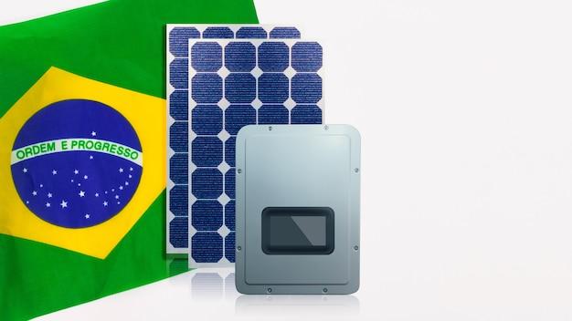 Painéis solares fotovoltaicos, inversor e bandeira do brasil isolado no fundo branco. espaço para texto