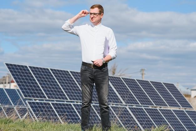 Painéis solares homem em pé perto de painéis solares
