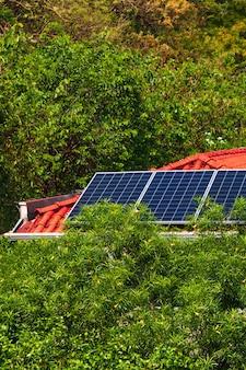 Painéis solares na casa de telhado vermelho em um dia ensolarado e nublado. imagem do conceito de instalação de energia solar fotovoltaica.