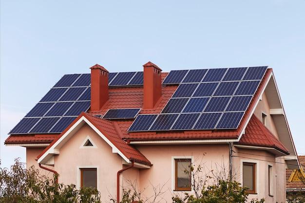 Painéis solares no telhado de uma casa particular são instalados ao redor da chaminé. energia alternativa
