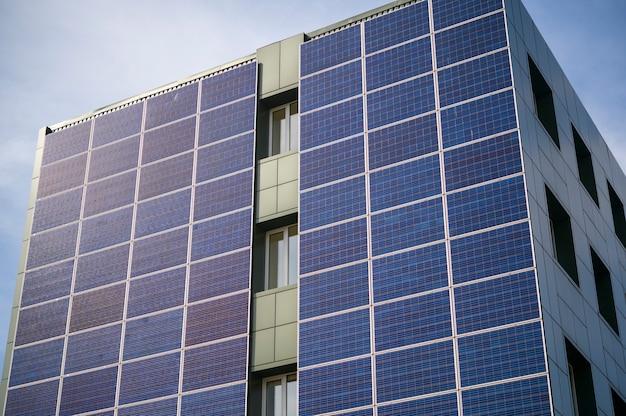 Painéis solares para geração de energia elétrica na parede de um prédio industrial da cidade durante o dia
