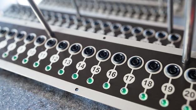 Painel de close-up com botões redondos numerados e entradas com plugues ao lado das antenas